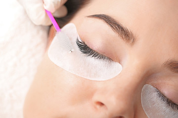 Young woman undergoing eyelash extension procedure in beauty salon, closeup