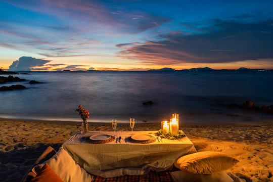 Romantic Dinner Table set beside the beach in the sunset twilight time, at Munnok Island, Thailand.