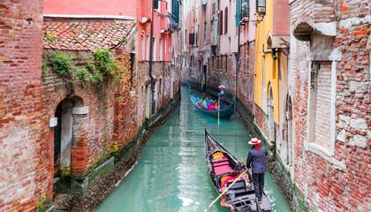 Foto auf AluDibond Venedig Venetian gondolier punting gondola through green canal waters of Venice Italy