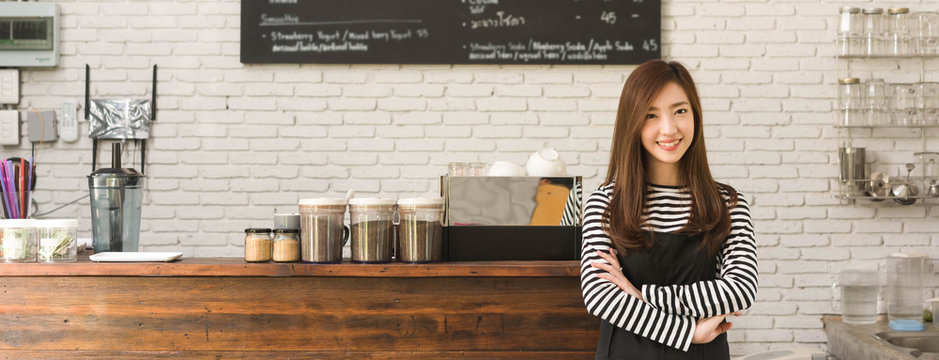 Young woman owner of a cafe stand in front of coffee counter, young entrepreneur conceptual, dimension image for banner
