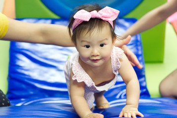 Young little cute Asian baby playing in kid's gym with her mother and teacher. She is crawling to the top of slider with support from her teacher. Child education and development concept.