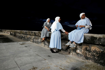 Nuns sit at the sea front in Havana