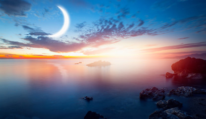 Wall Mural - Crescent moon rising above calm sea in sunset sky