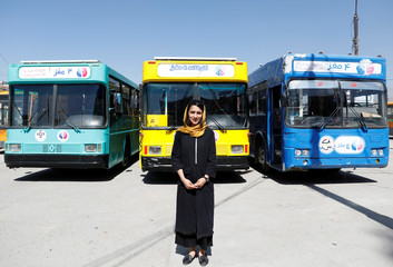Freshta Karim poses for photos in front of mobile library buses in Kabul