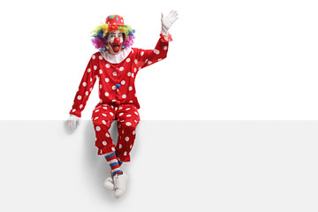 Funny clown sitting on a white panel and waving