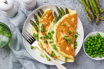 omelette with asparagus and green peas on white plate