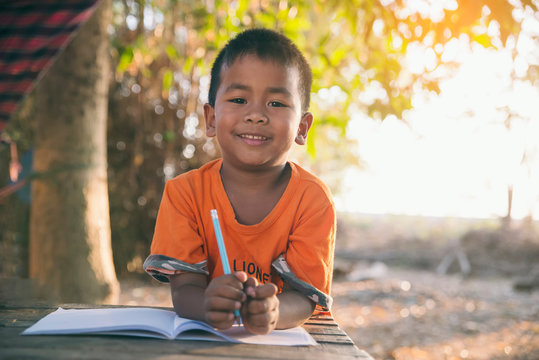 Asian child (poor kid) study at old home. Asia boy learning to draw, painting with color pencil. Poverty child, smile, lying on dirty wooden table and writing on books. Poor Quality Education Concept.