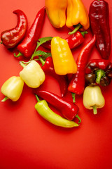 Yellow and red paprika on red background
