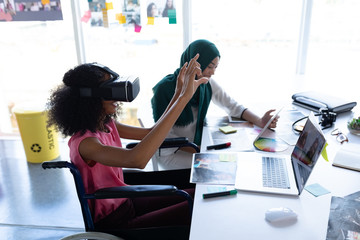 Female graphic designers using virtual reality headset and digital tablet at desk