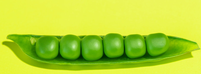 Fresh green pea pods and peas on the yellow background.