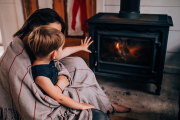 woman and toddler son sitting in front of fireplace