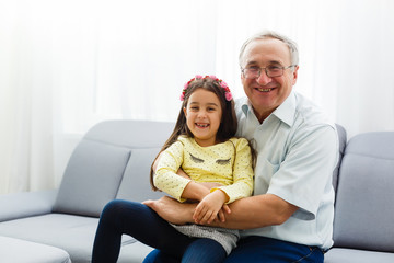 The happy girl hugs a grandfather on the sofa