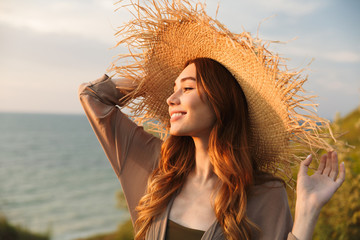 Beautiful young pretty woman in hat posing outdoors near sea on the beach. Wall mural