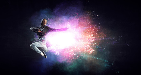 Modern female dancer jumping in hoodie with colourful splashes background. Mixed media