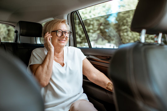Senior business woman talking with phone while sitting on the back seat in the modern car. Concept of a business life on retirement