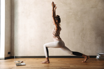 Photo of serious woman doing yoga exercises with closed eyes and palms together at home