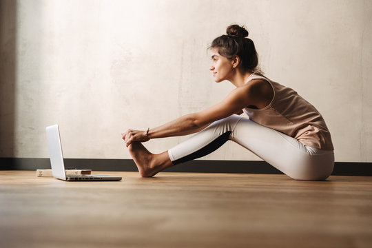 Photo of happy young woman doing exercises and using laptop while sitting on floor at home
