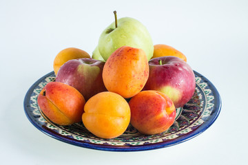 Fresh fruit on national Uzbek dishes with traditional ornament