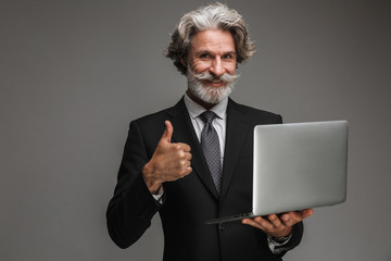 Image of handsome adult businessman wearing formal black suit showing thumb up and holding silver laptop