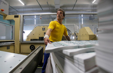 An employee adjusts sheets of 1000 Russian Rouble notes at Goznak printing factory in Moscow