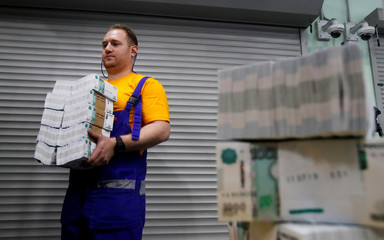 An employee carries packs of 1000 Russian Roubles notes at Goznak printing factory in Moscow