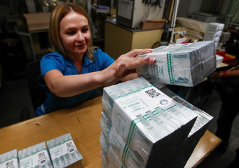 An employee adjusts packs of 1000 Russian Roubles notes at Goznak printing factory in Moscow