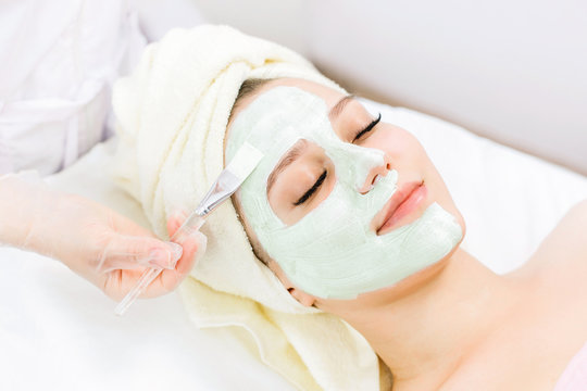 Portrait of beautiful woman laying with towel on the head. Young girl enjoys green cream facial mask. Lady getting spa treatment at beauty salon.