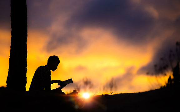 Silhouette of young male christian sitting and reading the holy Bible with light of sunset background, christian hope concept.