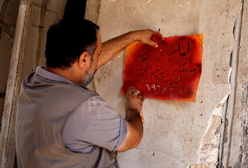 "Realtor stencils ""for sale"" on a house wall in the old city of Mosul"