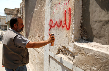 "Realtor writes ""for sale"" on a house wall in the old city of Mosul"