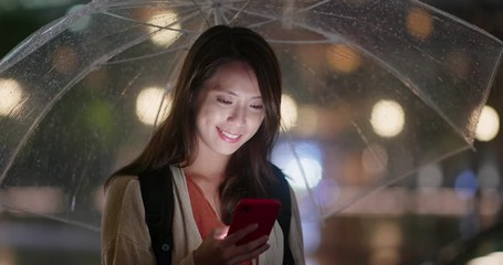 Wall Mural - Woman hold with umbrella and look at the cellphone at night
