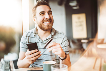 young man shopping online with credit card using smart phone in a cafe. Indoor concept of technology use