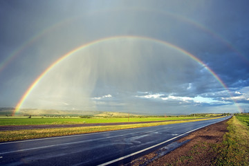 amazingly beautiful view of the rainbow on the horizon of the highway for cars