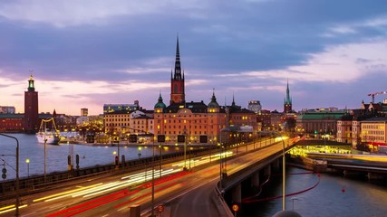 Fototapete - Stockholm, Sweden. Time-lapse of Gamla Stan in Stockholm, Sweden with landmarks like Riddarholm Church during the sunset. View of old buildings and car traffic at the bridge, zoom in