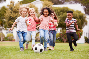 Group Of Children Playing Football With Friends In Park
