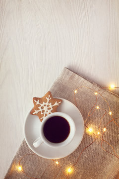 cup of espresso with a cookie next to the included garland on the table top view. holiday winter coffee break