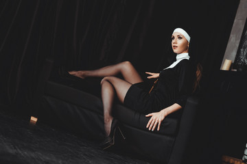 Sexy nun prays indoor . Beautiful young holy sister. Young beautiful nun with a cross in a robe in a black interior. Wall mural