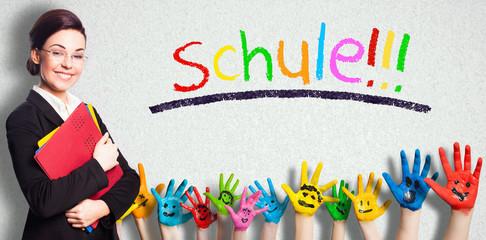 """junge lächelnde Frau für Wand mit dem Wort """"Schule!!!"""" in Kreideschrift und vielen angemalten Kinderhänden"""
