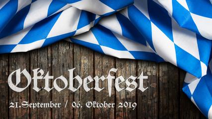 Oktoberfest 2019 Banner mit bayrischem Tischtuch auf Holzhintergrund