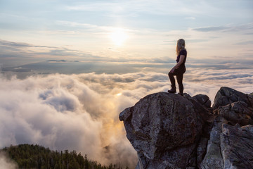 Wall Mural - Adventurous Female Hiker on top of a mountain covered in clouds during a vibrant summer sunset. Taken on top of St Mark's Summit, West Vancouver, British Columbia, Canada.