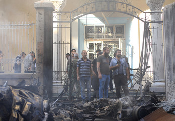 People gather at the site of a car bomb blast in front of a church in Qamishli