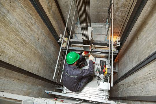 lift machinist repairing elevator in lift shaft