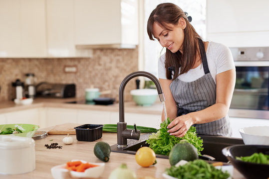 Cheerful attractive Caucasian woman in apron washing salad in kitchen. Dinner at home concept.