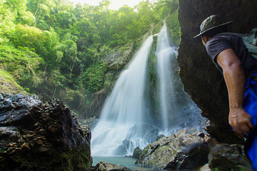 Men love to travel and hiking Adventure photographed young Thai people in Asia. Take yourself while walking on the Tam nang waterfall ,in the forest tropical zone,national park  Phang Nga Thailand.