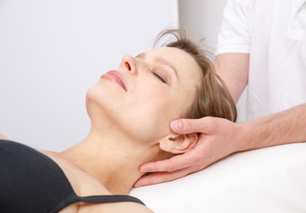 Woman receiving osteopathic treatment of her neck