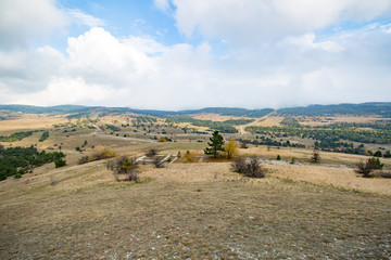 Panorama in autumn field, mountains, forest and grass