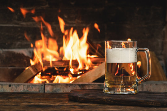 Beer in a mug on a wooden table on a burning fire in a fireplace background.