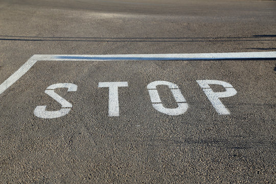 Stop - road marking on the asphalt at the intersection