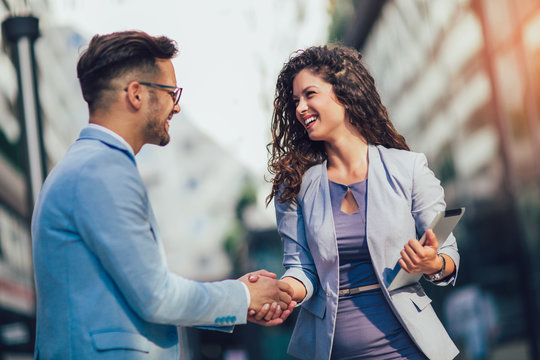Smiling business colleagues greeting each other outdoors
