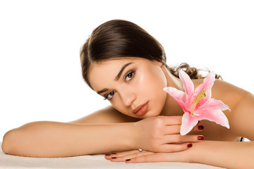 Young woman with makeup  posing with flower on white background